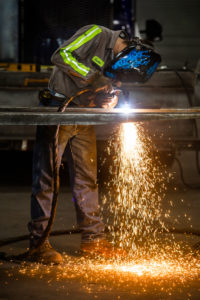 Welder working at a shop table on a piece of steel.