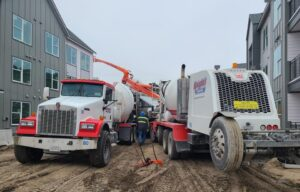 Mixer truck discharging in pump truck on a cold day.